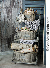 Background rustic veranda with a shelf with baskets and...