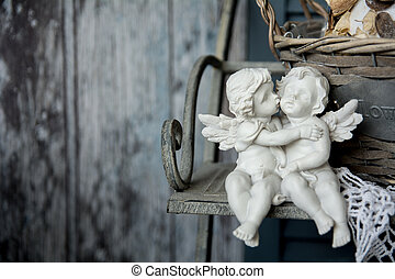 Figurines love angels sitting on a bench. Romance on the...