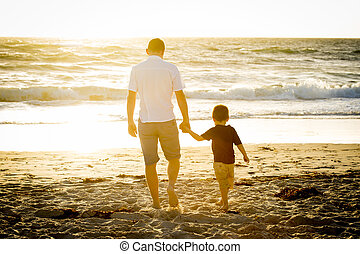 happy father holding holding hand of little son walking...