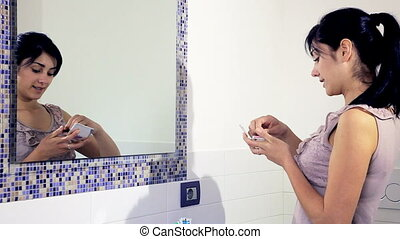 Woman in bathroom getting ready - Happy young woman putting...