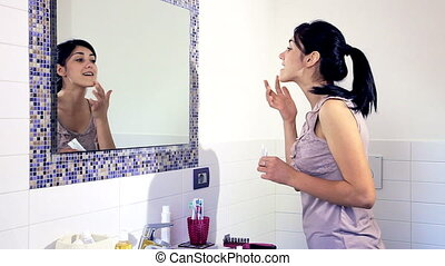 woman putting makeup in bathroom