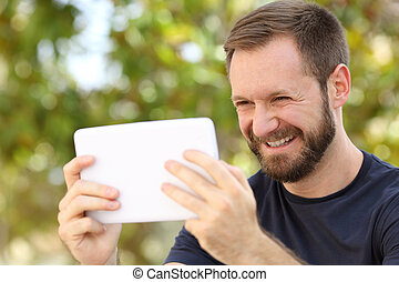 Happy man watching videos in a ereader tablet in a park with...