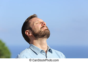 Man breathing deep fresh air outdoors with a blue sky in the...