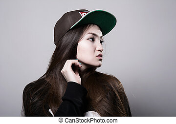 Young girl in a cap. Thoughtful girl rapper in the studio