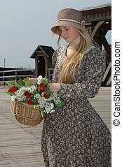 Girl with basket of flowers - Girl in gay dress and hat with...