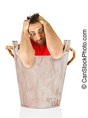 Man with a desperate expression in wooden bucket - Young man...