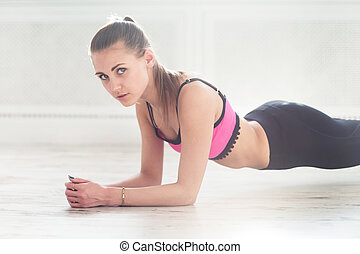 Slim fitnes young girl with ponytail doing planking exercise...