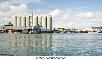 factory with patrol boat passing in harbour of port louis -...