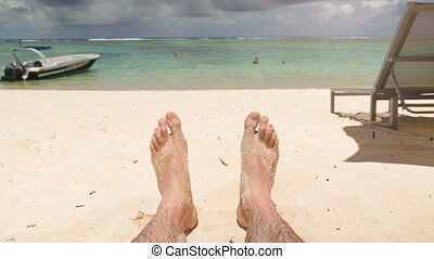 Happy feet at beach with boat in background - Man's feet at...