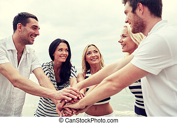 smiling friends putting hands on top of each other -...