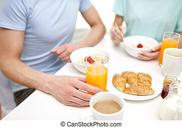 close up of couple having breakfast at home - food, eating,...
