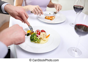 close up of couple eating appetizers at restaurant -...