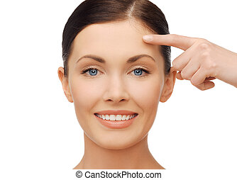 anti-aging concept - beautiful woman pointing to forehead