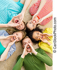 smiling people lying down on floor and screaming - education...