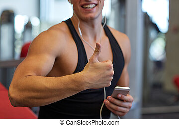 happy man with smartphone and earphones in gym - sport,...