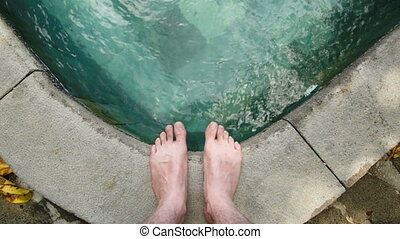 person standing at pool with focus on feet