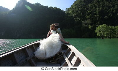 european wedding couple sitting in longtail boat - groom...