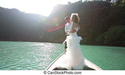 wedding couple standing on longtail boat