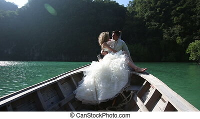 european wedding couple sitting in longtail boat - blonde...