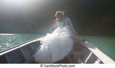 groom embraces bride sitting in longtail boat - blonde bride...