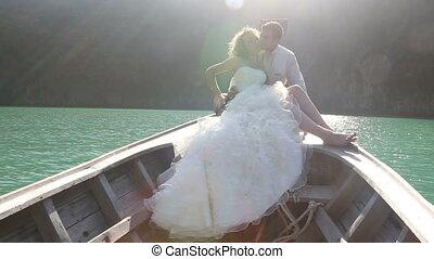 groom embraces bride sitting in longtail boat - groom kisses...