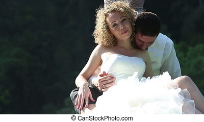 groom embraces bride sitting in longtail boat