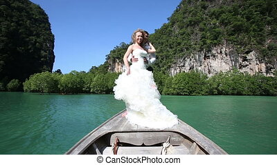 blonde bride waves hand standing on longtail boat - blonde...