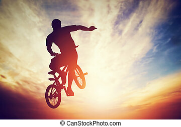 Man jumping on bmx bike performing a trick against sunset...