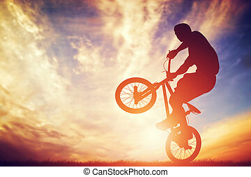 Man riding a bmx bike performing a trick against sunset sky....