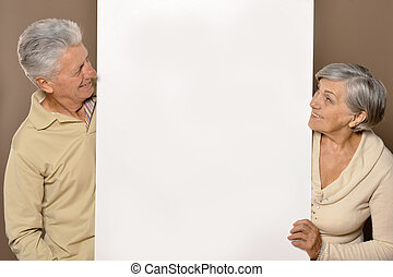 Old age couple holding blank banner and against white...