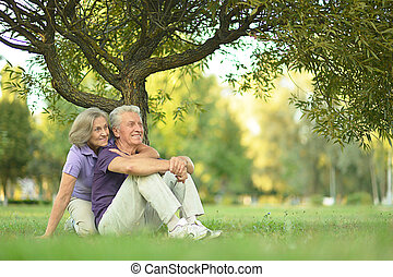 Happy Mature couple sitting in the park in summer day