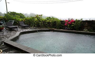 Raining in summer with pool - tropical rain coming down in...