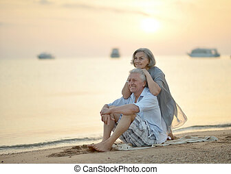 Mature couple relaxing on beach - Happy Mature couple...