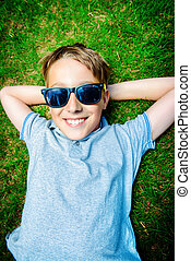 schoolboy summer - Cool boy lying on a grass at a park and...