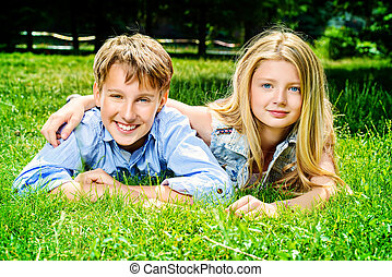 couple friends - Two cheerful teenagers on the grass in the...