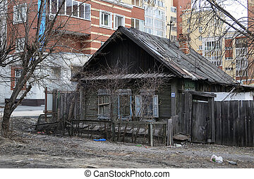 Old wooden houses against modern high-rise buildings Tyumen,...
