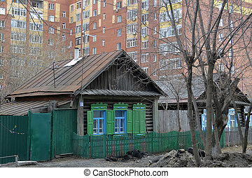 Old wooden houses against modern high-rise buildings....