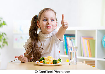 child eats healthy food showing thumb up - child girl eats...