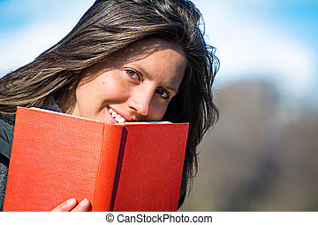young woman reading book - portrait of a girl with a red...