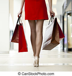 Legs of shopaholic wearing red dress while carrying several...