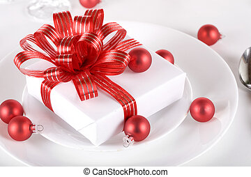 White present with red ribbons on a dinner plate, christmas...