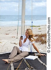 Beautiful Young Woman Sending Text On Boat At The Beach