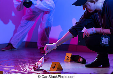 Working on a murder scene - Image of policewoman working on...