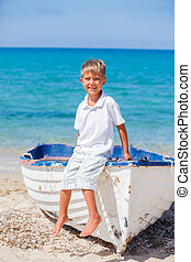Boy with boat - Cute little boy near boat on the beach