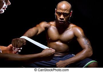 Motivated Black Fighter Preparing with Athletic Tape -...
