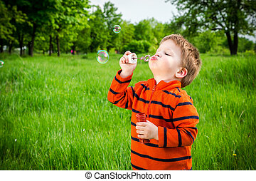 Little boy with soap bubbles - Little boy blowing up the...