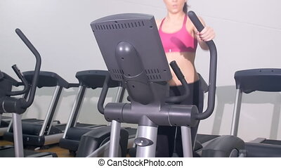 woman exercising on cross trainer - young fit woman...