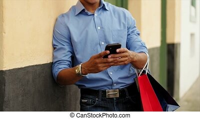 African American Man Shopping And Text Messaging On Phone -...