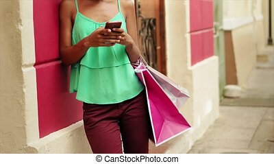 African American Girl Shopping And Text Messaging On Phone -...