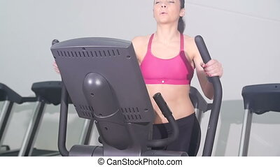 woman working out on cross trainer - young fit woman...